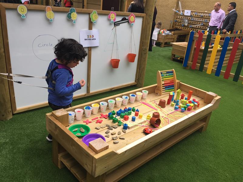 Child looking at a construction table with art and crafts materials on top