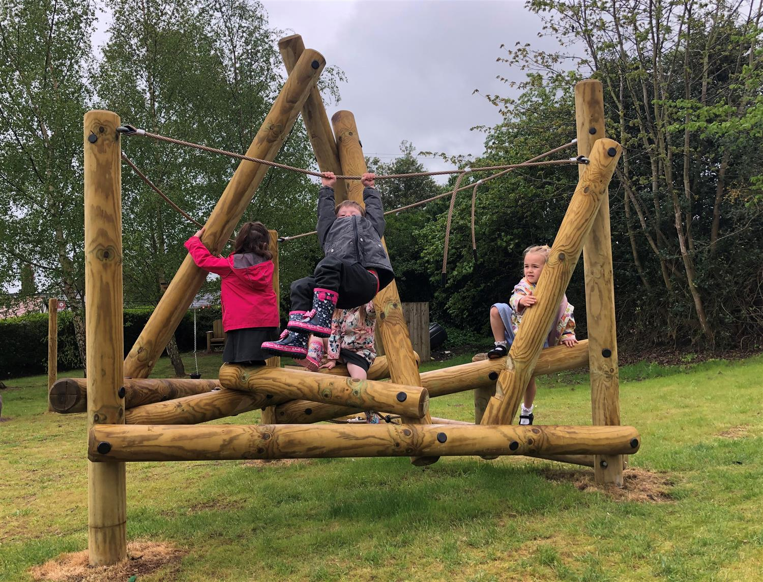 Children playing on a school climbing frame in the rain