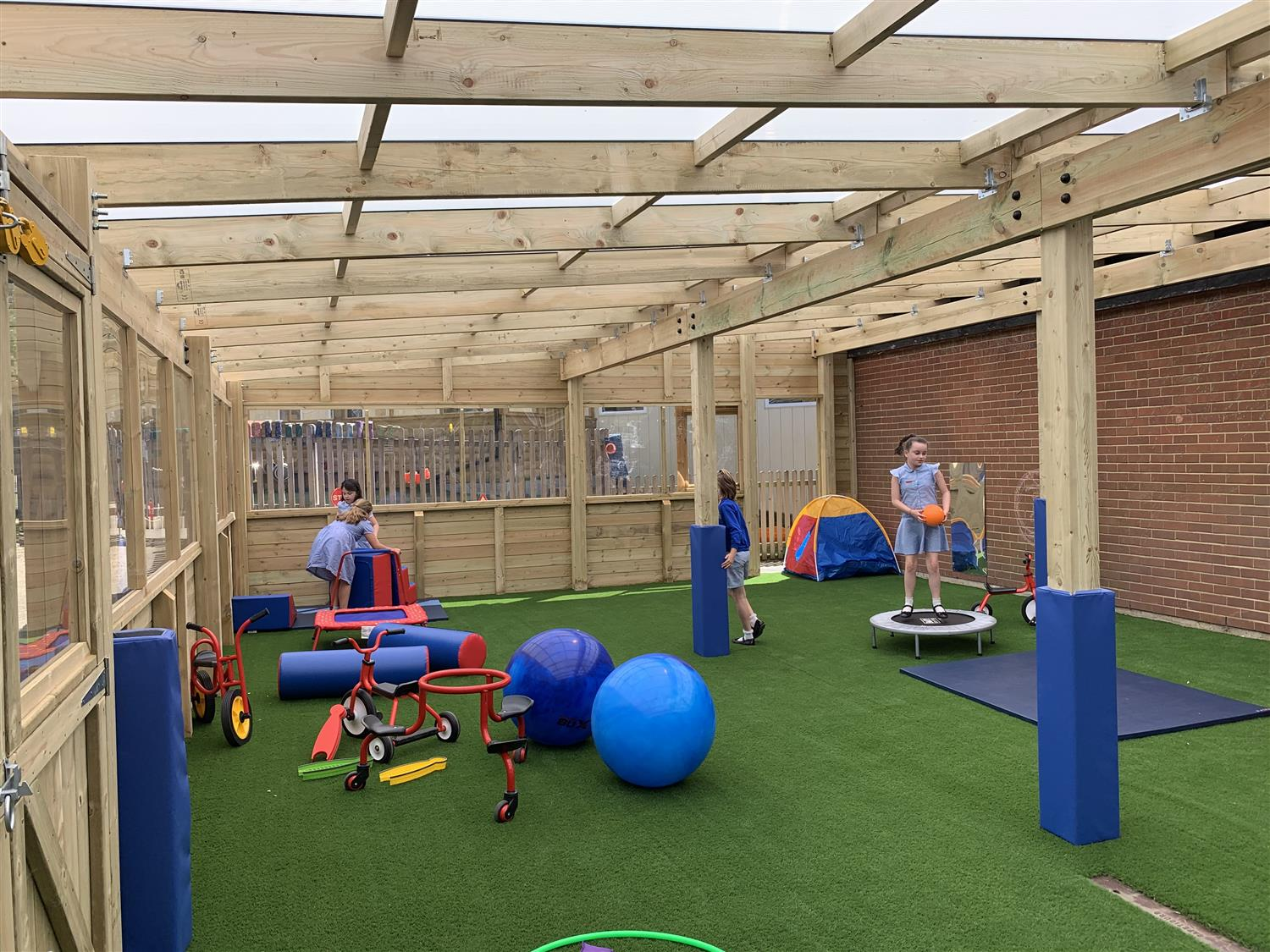 Children playing on artificial grass underneath a timber canopy
