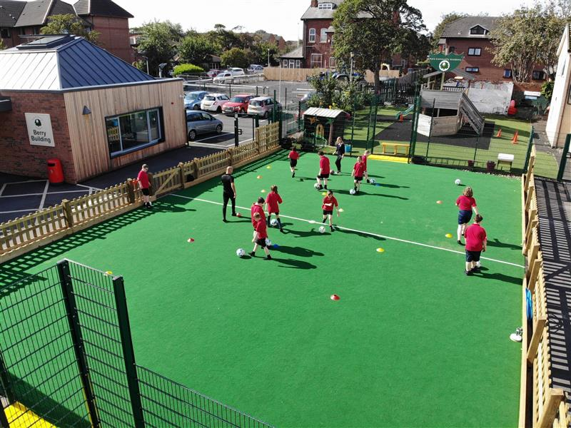 Children playing football games on a multi use games area with a teacher coaching the lesson