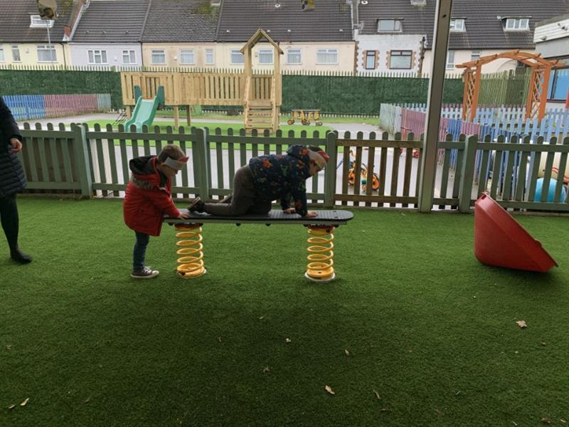 Two children crawling across a spring plank installed onto artificial grass surfacing