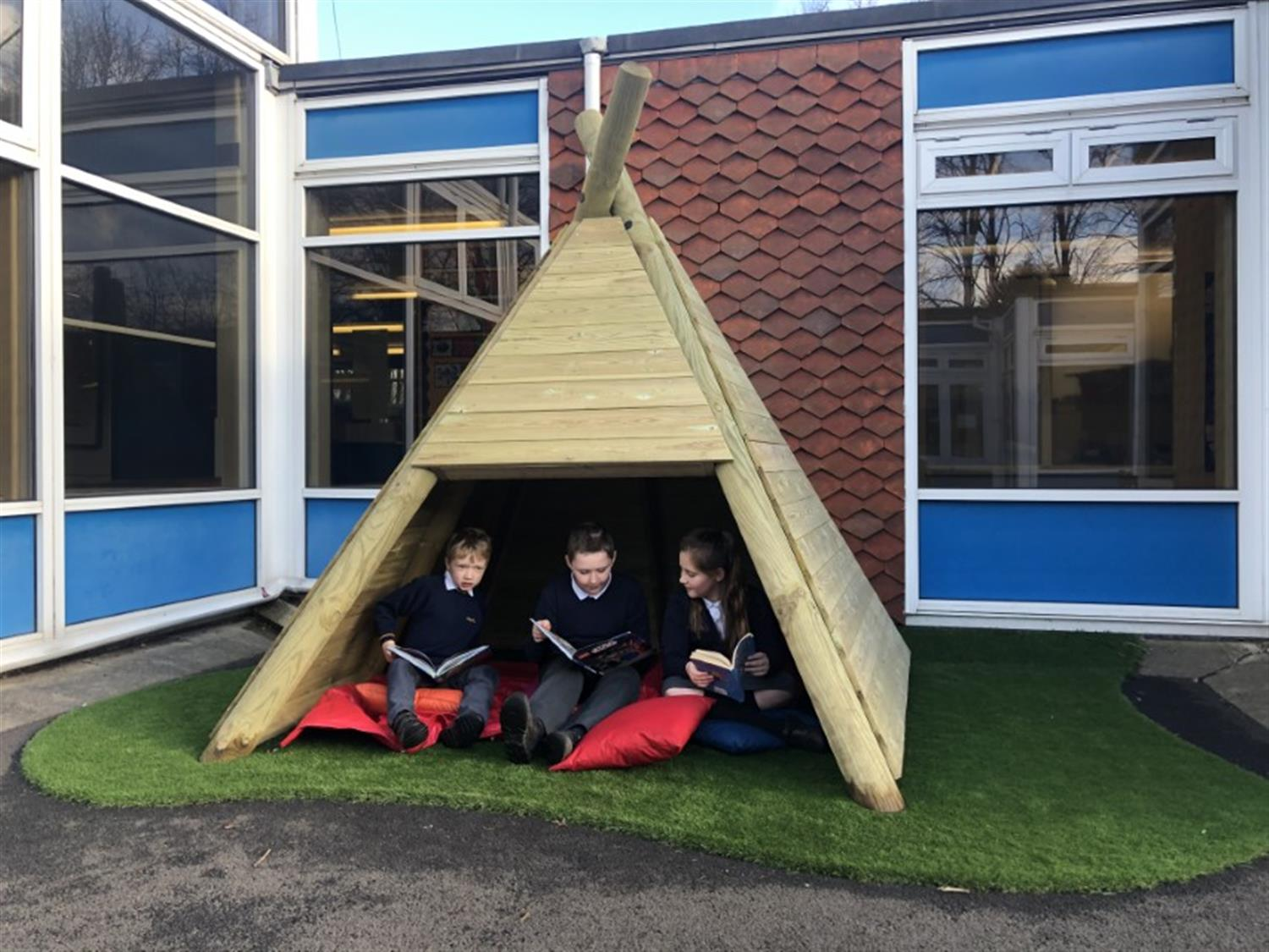 children reading in a playground den