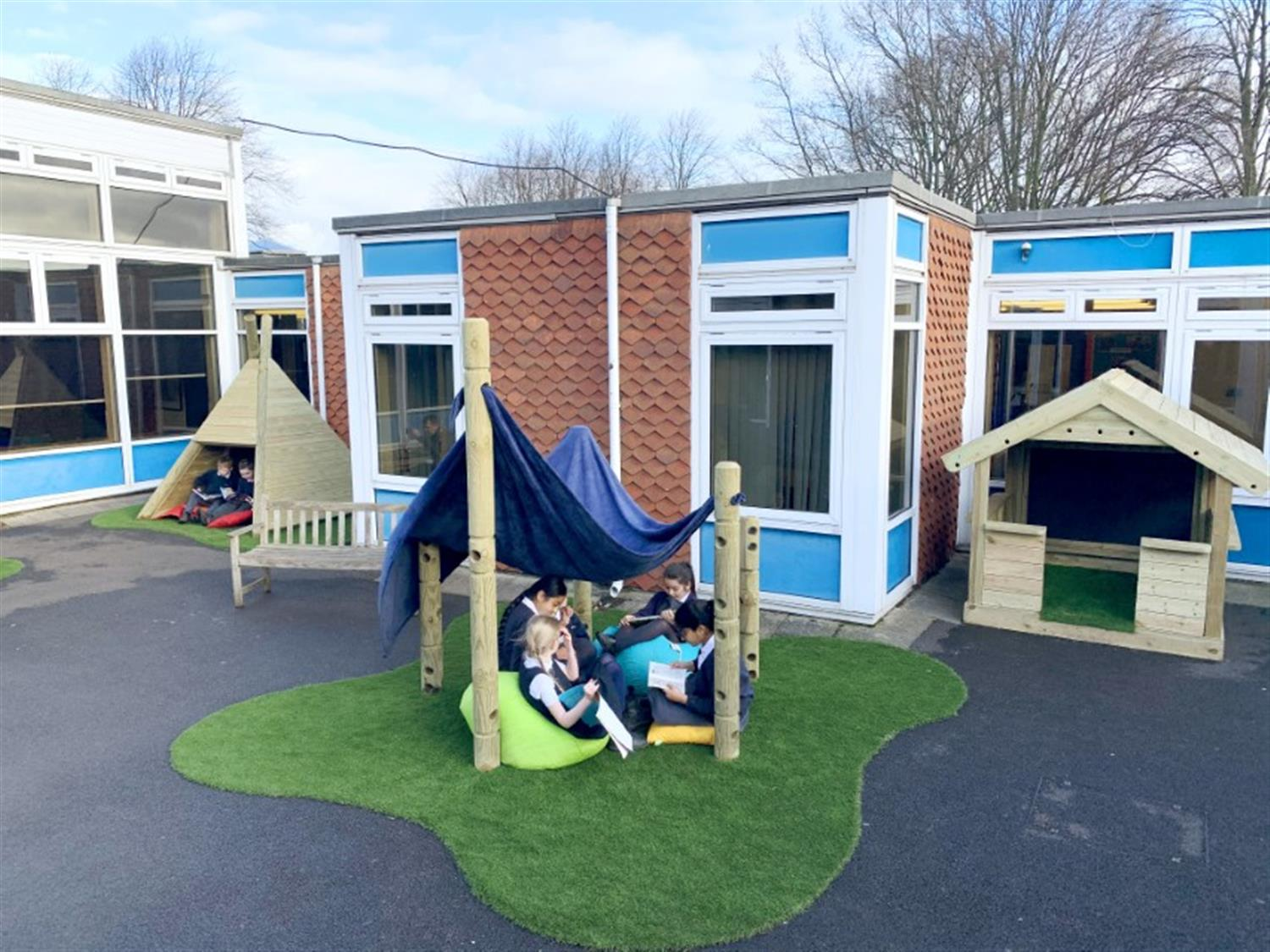 children sitting in a playground den created by den making posts