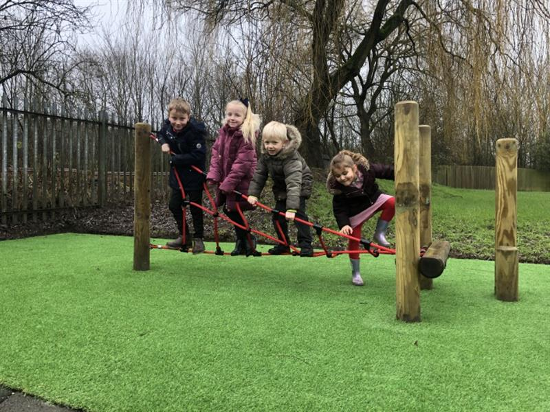 4 children standing on a twist net, balancing and gripping and grasping the red ropes