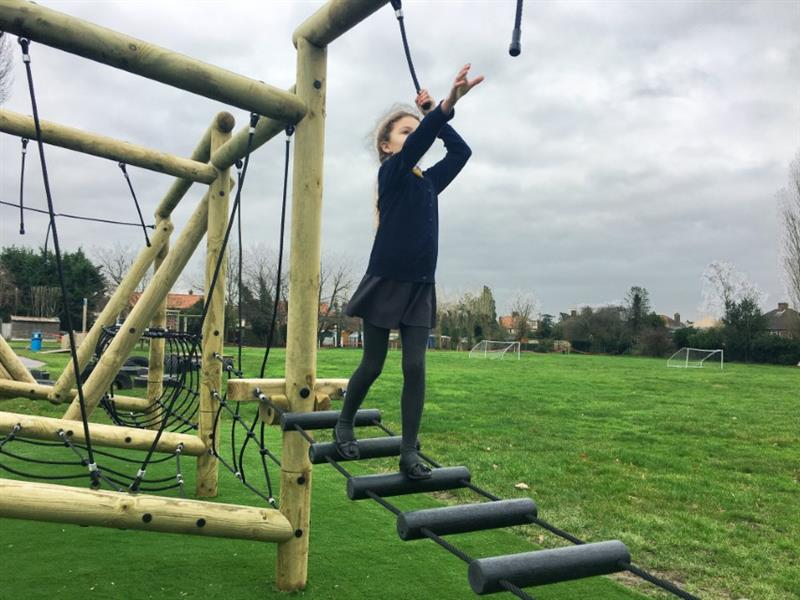 A child tackling the challenges on pentagon plays grizedale forest circuit and reaching for the ropes as they balance carefully across an obstacle