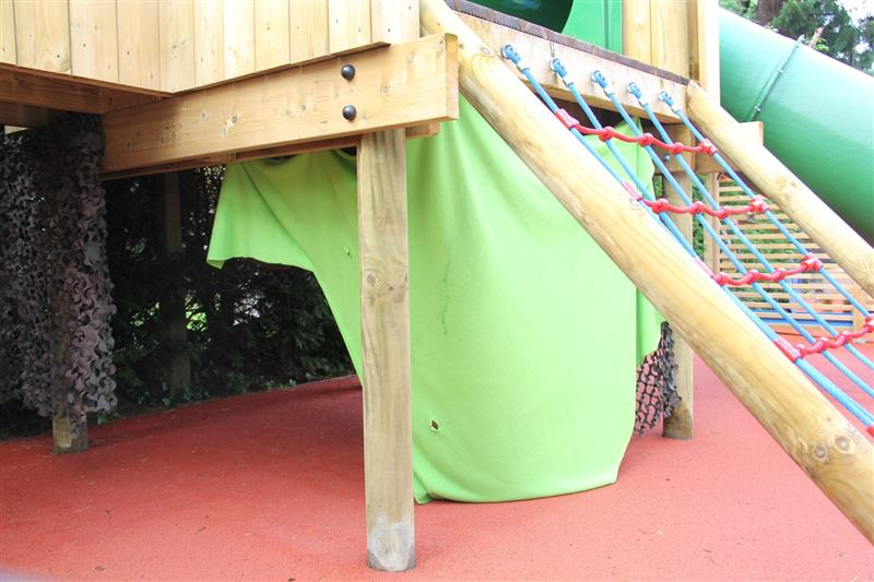 A creative den made using a lime green sheet and camouflage netting underneath a large timber play frame which has been installed onto red surfacing with a green slide attached to the play frame.