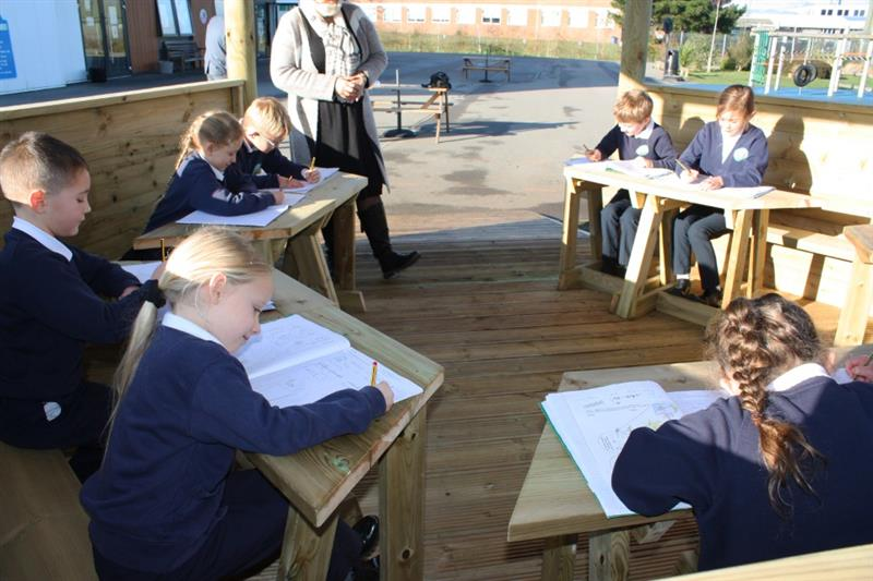 Children sat at work stations in a timber outdoor gazebo working in their work books
