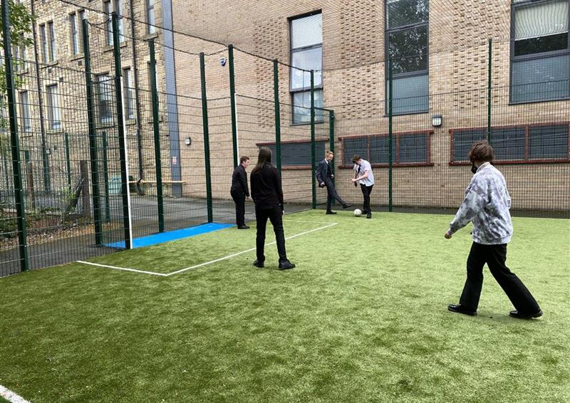 5 children playing on a recently installed MUGA at their school, one young boy is in the net and the rest are playing football.