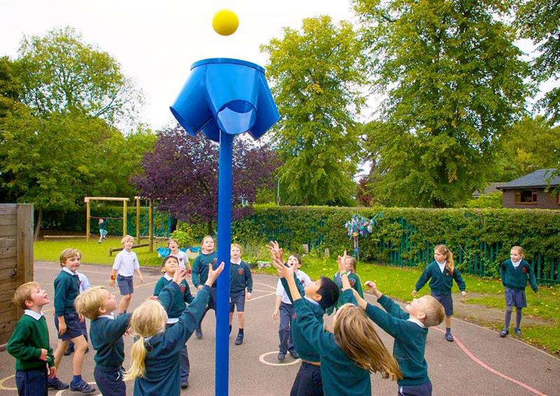 A class of children trying to throw and catch the ball into their 4 way ball shoot, the ball shoot is blue.