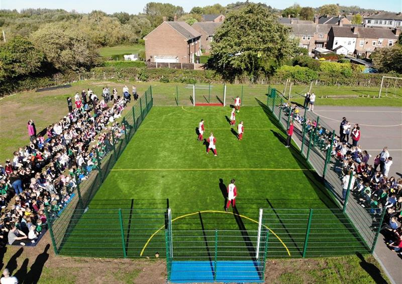 A birds eye view of a football match occurring on a MUGA, with a crowd surrounding the multi-use games area.