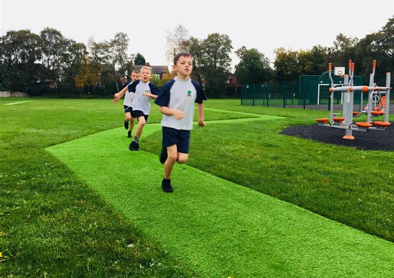 3 children running on their new daily mile track, the daily mile track is green artificial grass, with grass surround the outside.