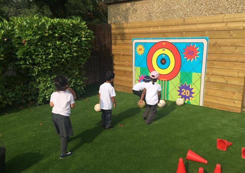 4 children playing on artificial grass in front of the goal target, the wall target starts at 10 and ends at 40 as a bullseye.