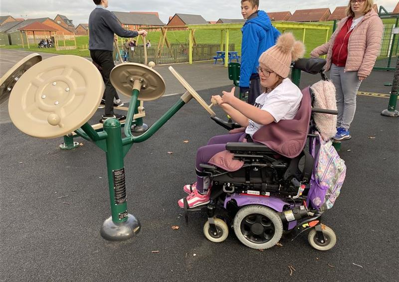 A girl in a wheelchair using one hand to move the tai chi spinner, a girl and two boys are stood behind her.