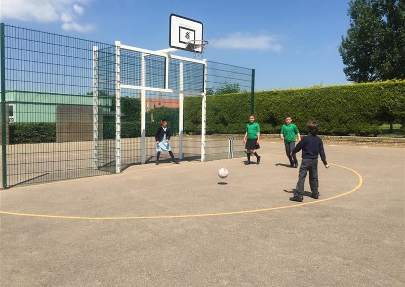 3 children playing football aiming at the maxi goal, one girl is stood within the goal posts waiting to save the ball.