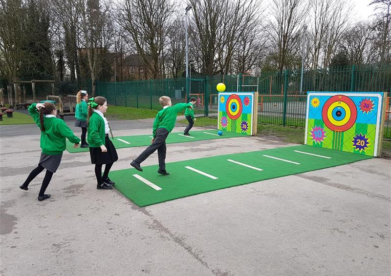 Two goal targets on a playground, with green Saferturf leading from the target with white marking lines. on the front goal target there are 3 children throwing a ball and on the furthest away target there are 2 children throwing a ball.