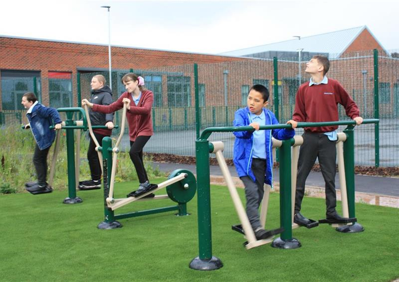 5 children playing on their outdoor gym, 2 children are on a double air walker and one girl is on a cross trainer, the other two boys are playing in the background.