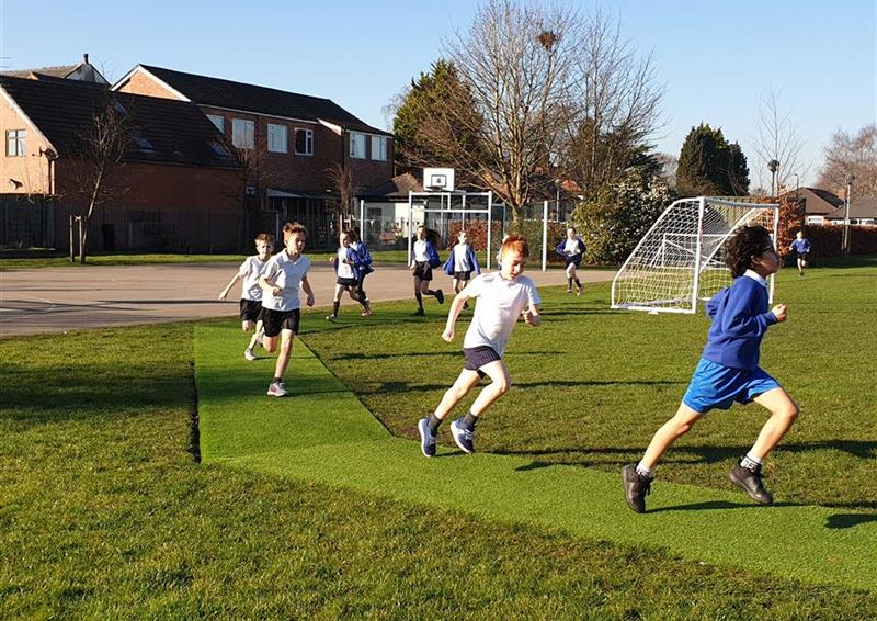 A class of children running on their daily mile track, in the middle of the daily mile track there is a goal with grass surrounding the track.
