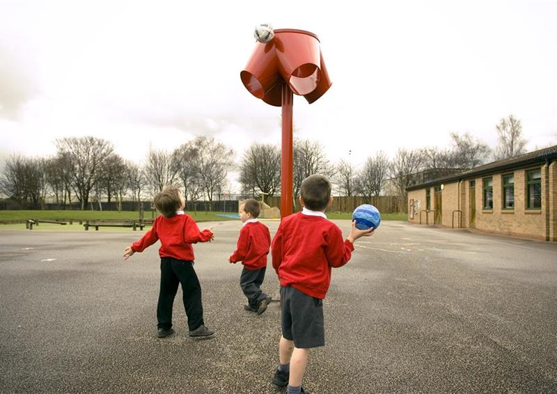 3 young boys throwing a ball into a red 4 way ball shoot, one boy is holding the ball.