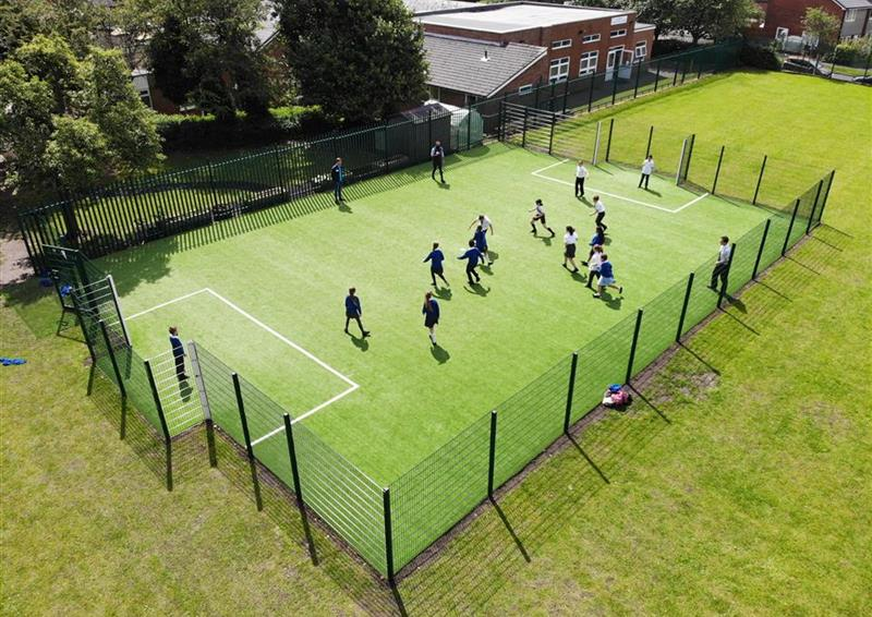 A birds eye view of a class of children playing on their multi-use games area.