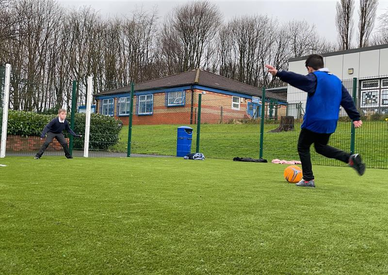 2 children playing on their multi-use games area, one boy is in net waiting to save the goal and the other young boy is taking a shot towards the goal