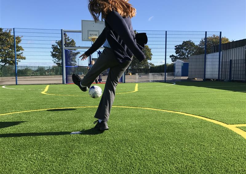 A girl taking a shot towards the goal on the multi-use games area at school.